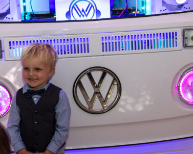 Smiling and taking photographs with the VW DJ booth supplied by Wedding DJ Cornwall.