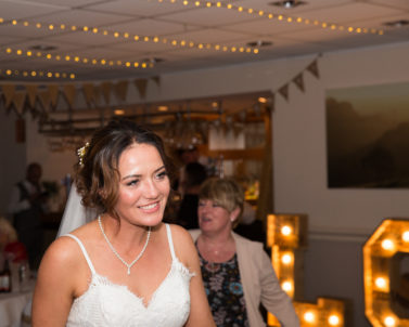 A beaming bride on the dance floor with wedding DJ Cornwall in control of the music
